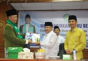 Foto: Guru Besar Ekonomi Islam yang juga merupakan Rektor UIN Suska Riau menyerahkan salah satu hasil karya kepada Dekan FSH Uin SUSKA Riau